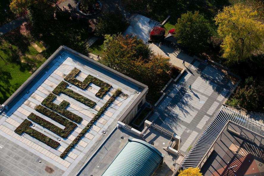 The word Tufts is spelled out in grass and bushes on the roof of the Tisch Library