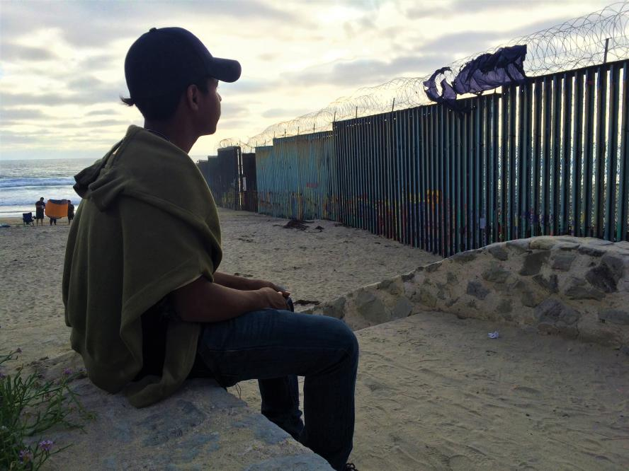 A boy sits on a beach in Tijuana, Mexico and looks at the US border wall
