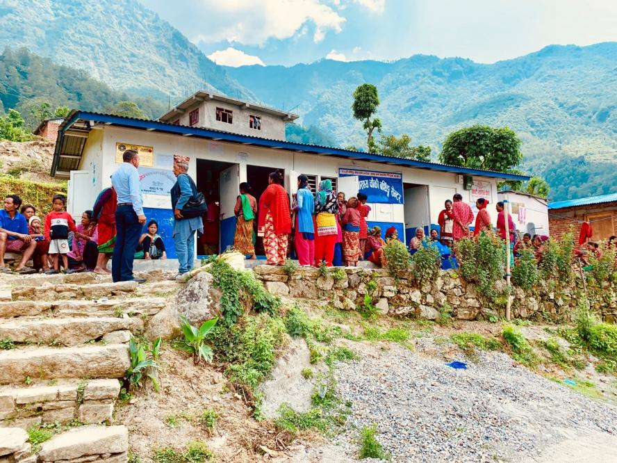 People stand outside of a rural medical clinic in the mountains in Nepal