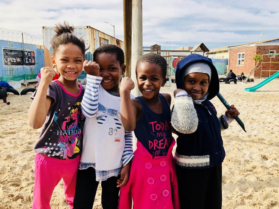 Four little girls show their arm muscles in one of the oldest and poorest settlements in the Cape Town, South Africa