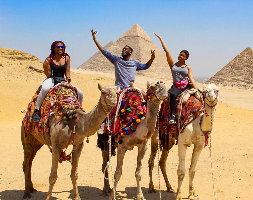 Three Tufts students ride on camels in front of pyramids in Egypt