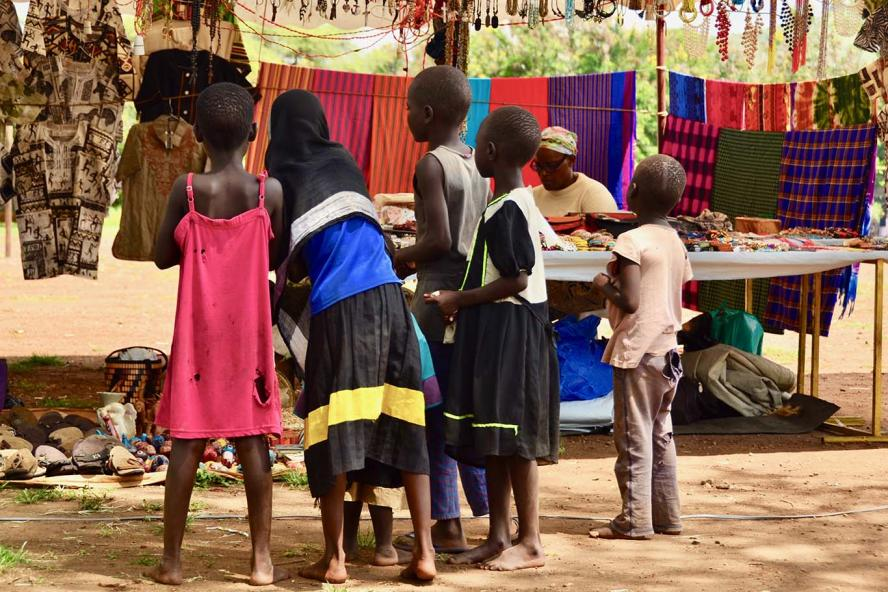 Children at a market, standing in front of a vendor