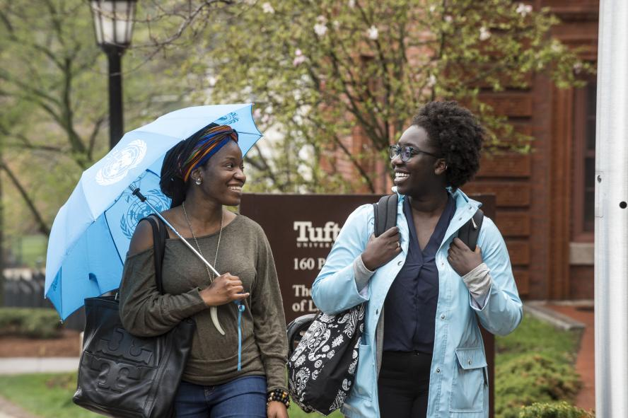 two students walking and talking on Tufts' campus on a rainy day