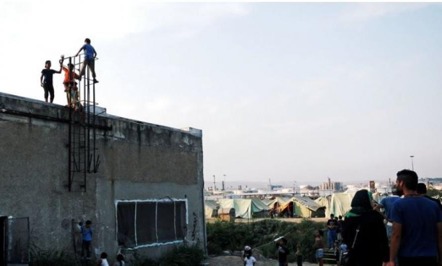 People climb a metal ladder up the side of a building, while others look over a tent city