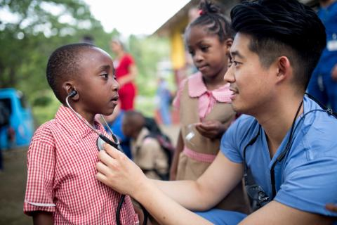 A dental student listens to a little boy's chest with a stethoscope in Jamaica