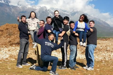 Tufts students in China standing in front of a mountain range