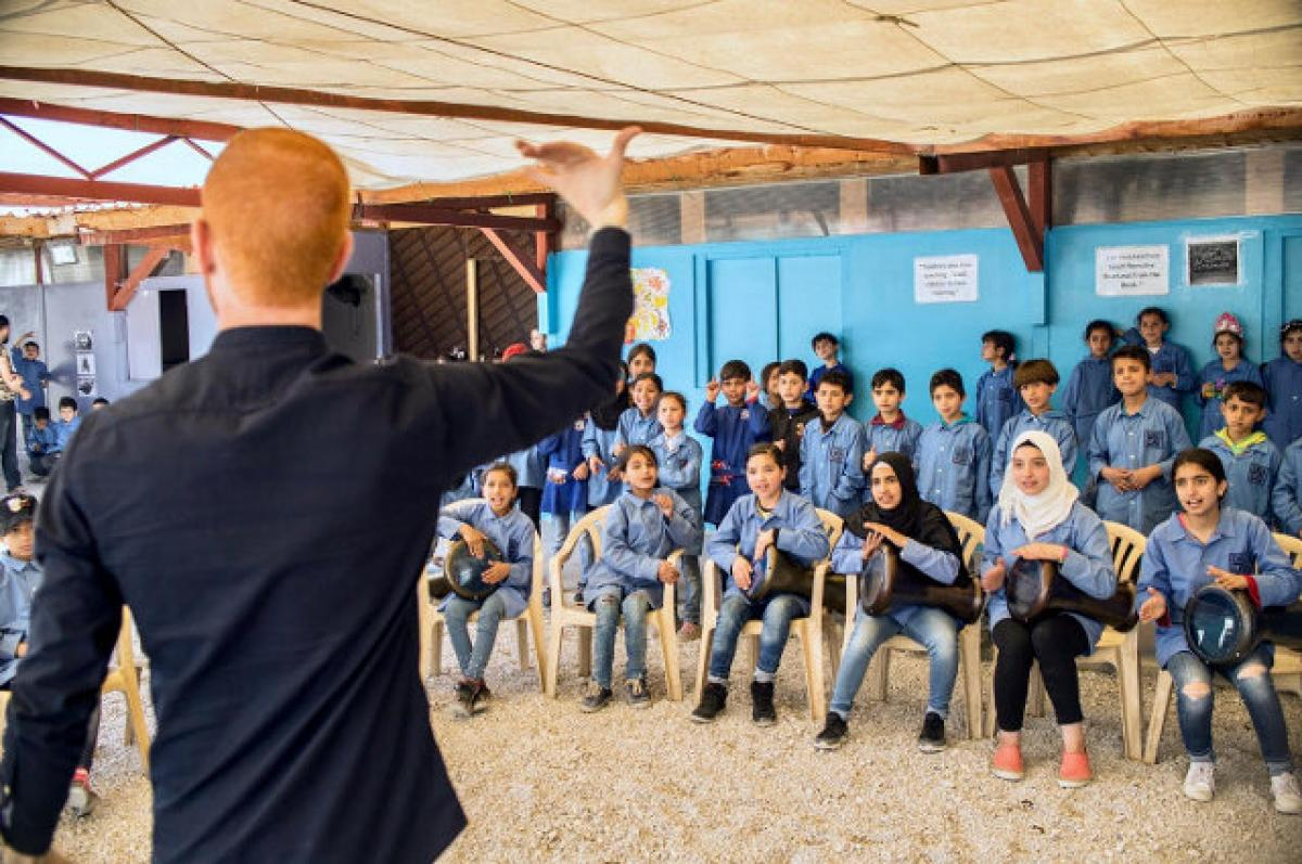 Layth Sidiq, Lecturer of Music at Tufts, conducting a group of Syrian refugee children