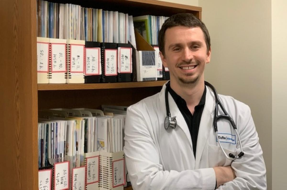 Tufts medical student Emal Lesha in his white medical coat, with a stethoscope around his neck