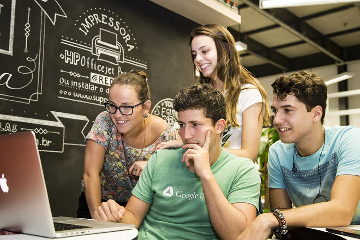 Students gather around a computer monitor. A chalkboard in the background has words written in Portuguese.