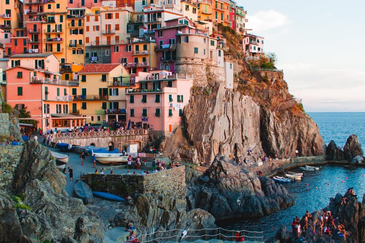 Colorful houses are built into the Italian cliff, overlooking a harbor with boats